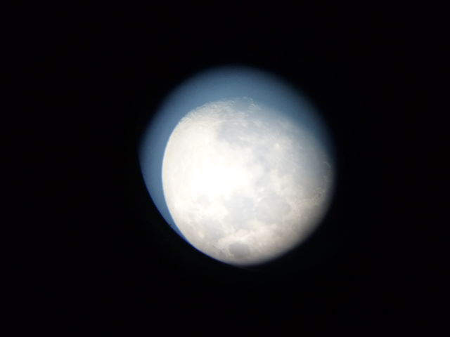 Hand held image of the moon through telescope